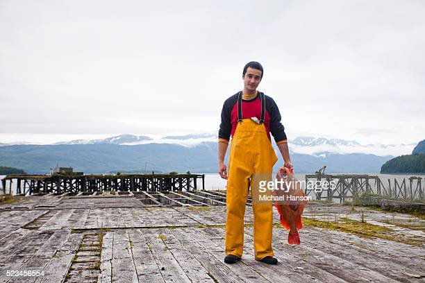 young fisherman holding large red fish on wooden dock - fisherman stock pictures, royalty-free photos & images