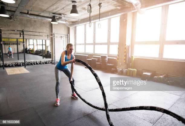 Jonge aantrekkelijke vrouw passen in sportschool werken haar armen en terug met staaf-van-barbell.