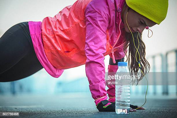 Young fit determined woman exercising push-ups after running