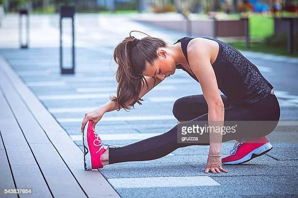 Jeune fit déterminé femme qui s'étend de sa jambe après le travail