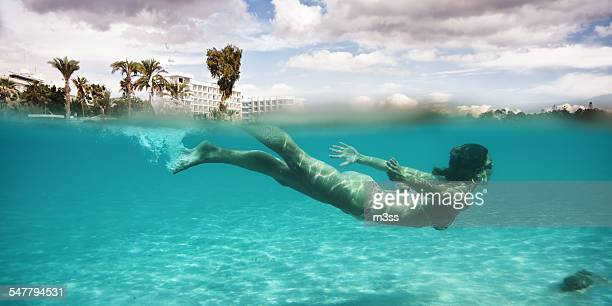 Young fit girl swimming undersea in shallow water