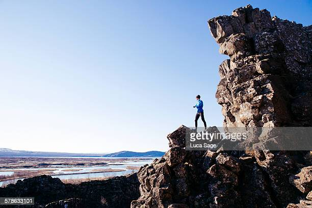 A young fit male looks out over mountain and lake