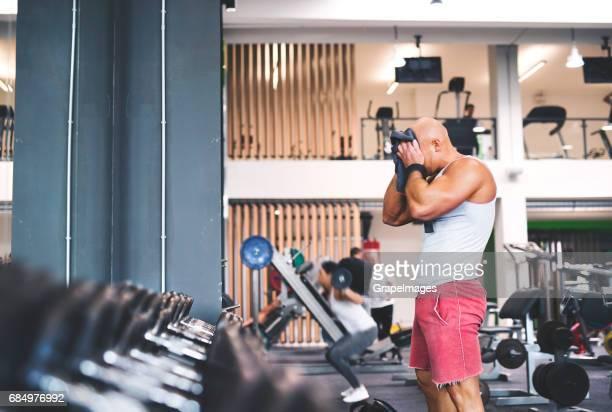 Junge fit Mann im Fitness-Studio, Reihen von Metall Hand Hanteln auf Gestell vor ihm.