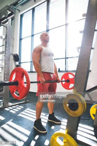 Young fit man in gym working out with heavy barbell, doing dead lift