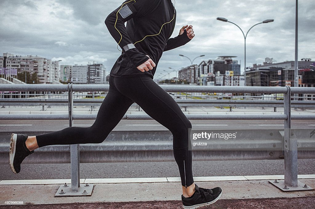 Young fit man running and listening to music : Stock Photo