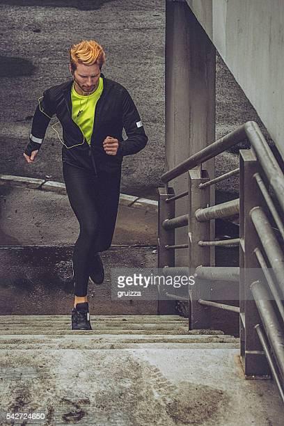 jungen fit mann läuft in einem städtischen ambiente. - wurf oder sprungdisziplin herren stock-fotos und bilder