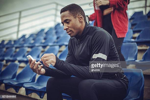 Young fit man texting at the stadium after strenuous workout