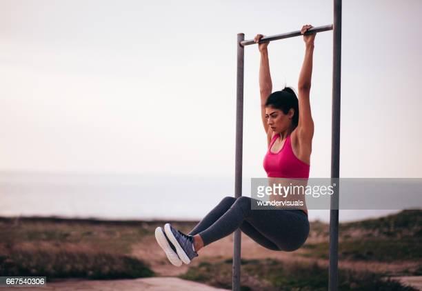 Joven mujer haciendo ejercicios de abs en el exterior de la barra horizontal de ajuste