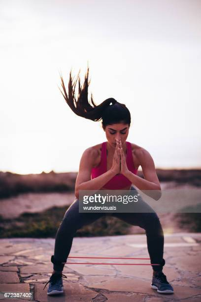 Young fit woman doing exercise with resistance band outdoors