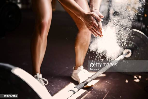 young fit woman getting ready for lifting weights in a gym - magnesium stock pictures, royalty-free photos & images