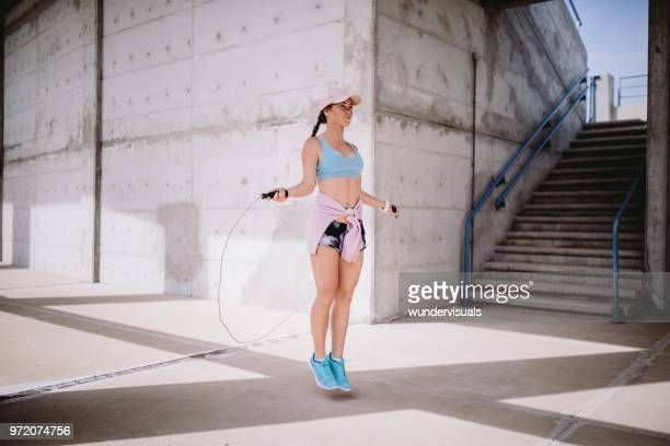 young fit woman in sportswear skipping rope and exercising outdoors - skipping along stock pictures, royalty-free photos & images