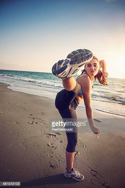 Junge fit Frau treten bis Bein am Strand bei Sonnenuntergang.