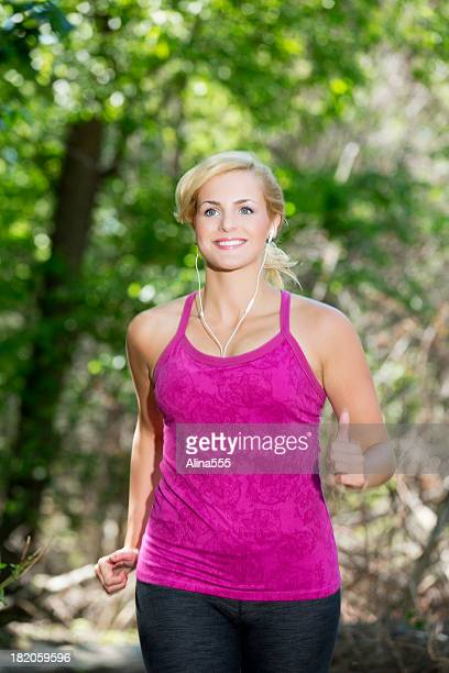 Young fit woman power walking through the woods