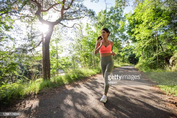 young fit woman running in forest at sunny day. - one young woman only stock pictures, royalty-free photos & images