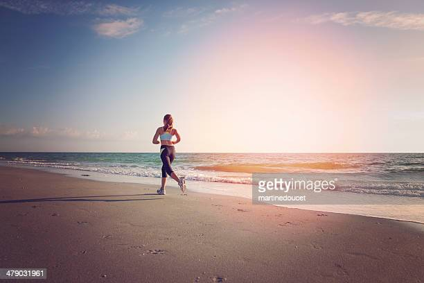Young fit woman running on the beach at sunset.