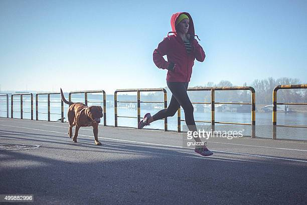 Young fit woman running with her dog on the riverbank