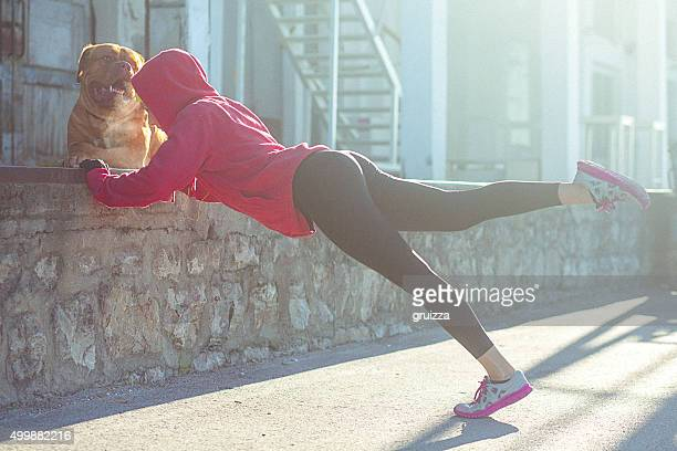 Young fit woman stretching after running