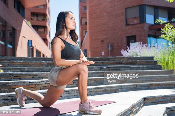 young fit woman stretching after training. - one young woman only stock pictures, royalty-free photos & images