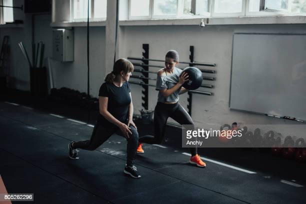 young fitness coach tells adult woman to copy her pose - daughters of darkness stock pictures, royalty-free photos & images