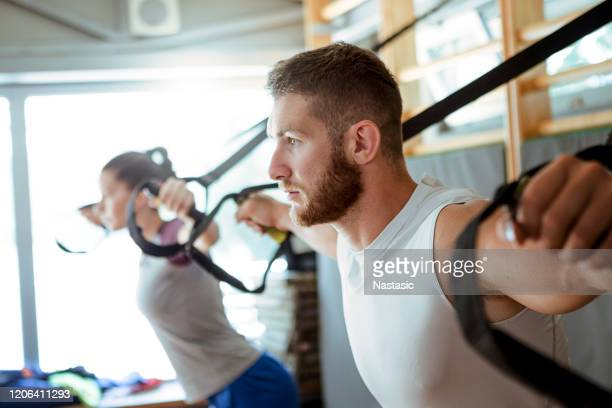 young fitness couple workout with trx straps - strap stock pictures, royalty-free photos & images
