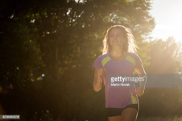 Young fitness enthusiast jogging outdoors in the sunshine
