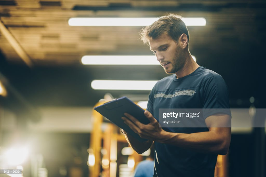 Young fitness instructor reading a training plan in a gym. : Stock Photo