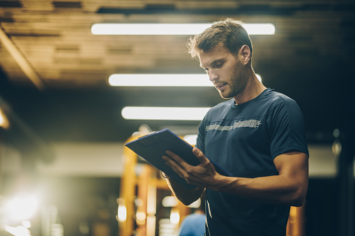 Young fitness instructor reading a training plan in a gym. 942145636
