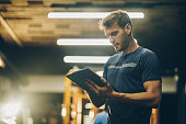 Young fitness instructor reading a training plan in a gym.