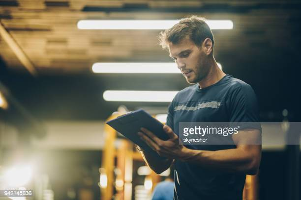 young fitness instructor reading a training plan in a gym. - coach stock pictures, royalty-free photos & images