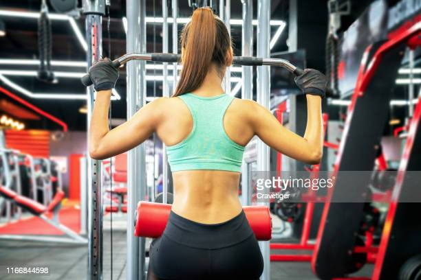 young fitness woman execute exercise with exercise-machine in gym, horizontal photo.exercising, gym, sport, girl, body care, day, sports clothing, indoors, exercise machine, form, health club, sports training, gymnasium, - fat belly girl stock photos and pictures