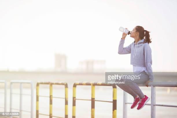 Femme jeune de remise en forme au repos après en cours d'exécution et de l'eau potable