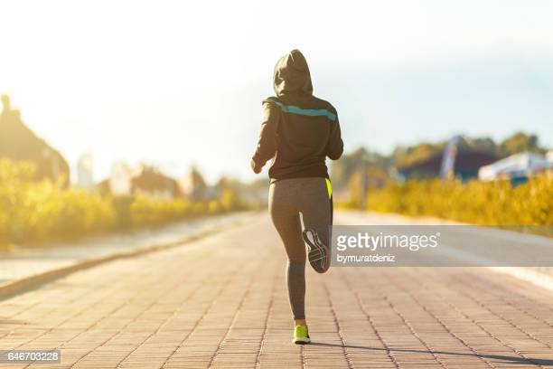 Young fitness woman runner athlete running on road