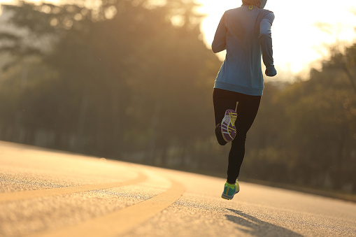 Young fitness woman runner running on sunrise road 1156227790