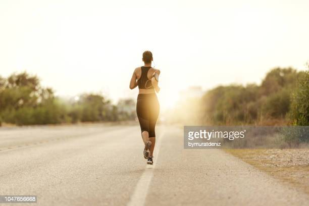young fitness woman running at road - marathon stock pictures, royalty-free photos & images