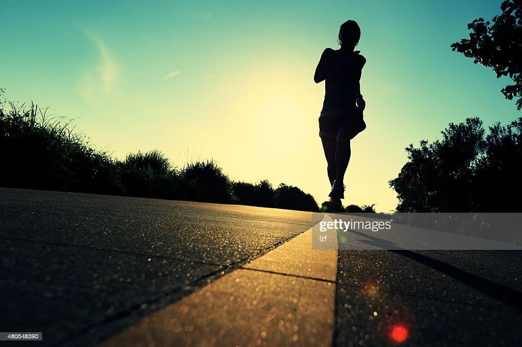 young fitness woman running on sunrise seaside trail : Stock Photo
