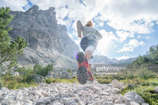 young fitted woman trail running in the dolomites, italy - cross country running stock pictures, royalty-free photos & images