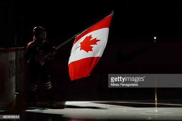 A young flag bearer waves the Canadian flag during the pre game ceremony prior to the 2015 IIHF World Junior Hockey Championship game between Team...