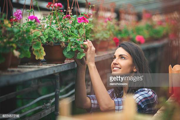 Young florist checking her plants in the greenhouse