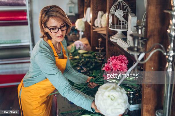 Young florist preparing a bouquet at her shop