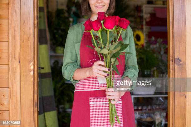 Young florist with bouquet of red roses in flower shop doorway