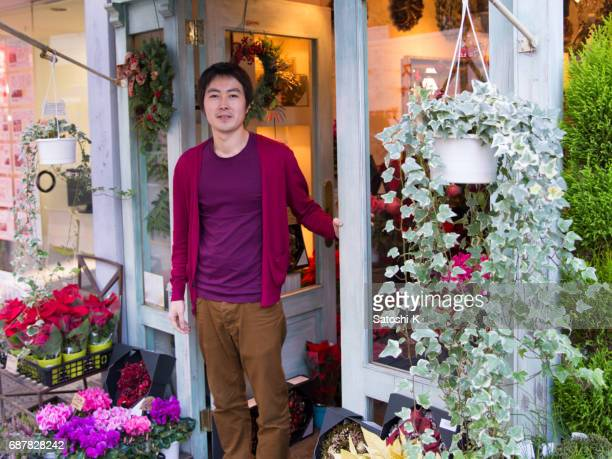 Young flower shop owner standing in front of shop entrance
