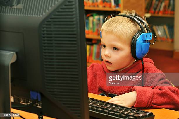 A young focused blond boy on a desktop computer