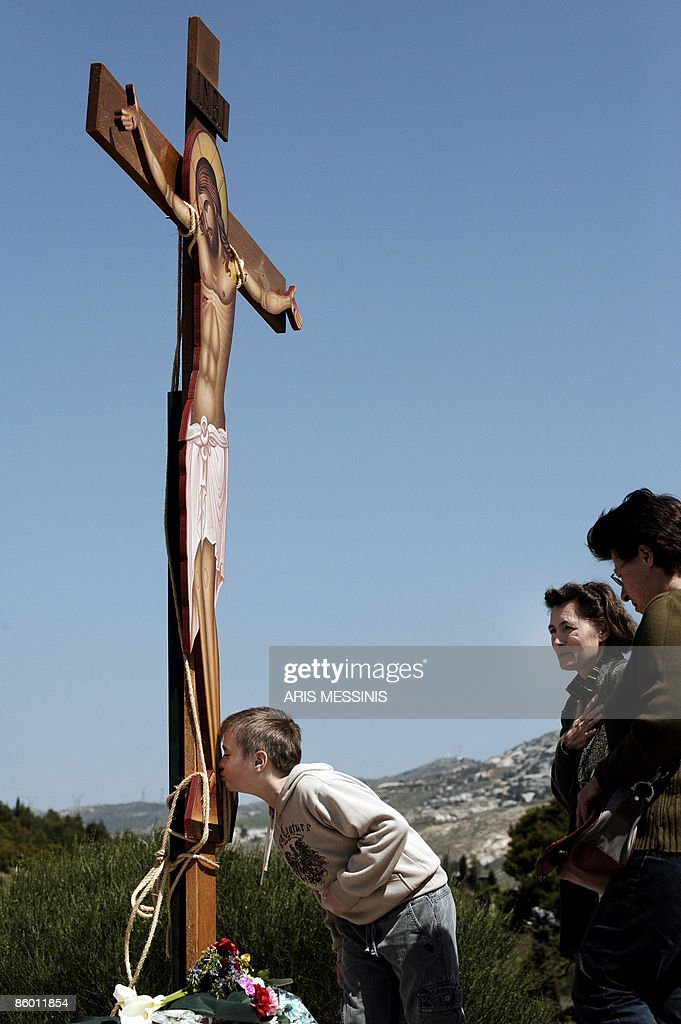 A young follower of the Greek Orthodox Church kisses the feet of an image of Jesus crucified during the ceremony marking the Apokathelosis, the removal of Christ's dead body from the Cross, which forms a key part of Orthodox Easter, in a ceremony at the Church of the Dormition of the Virgin in Penteli, north Athens April 17 2009. Millions of Greeks flock to churches around the country this week to celebrate Easter, the country's foremost religious celebration. AFP PHOTO / Aris MESSINIS