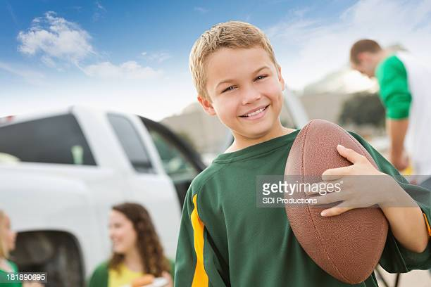 Young football fan at a tailgate party with his family