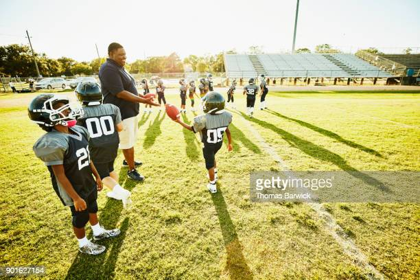 Young football player handing ball to smiling coach while running drills with teammates during practice