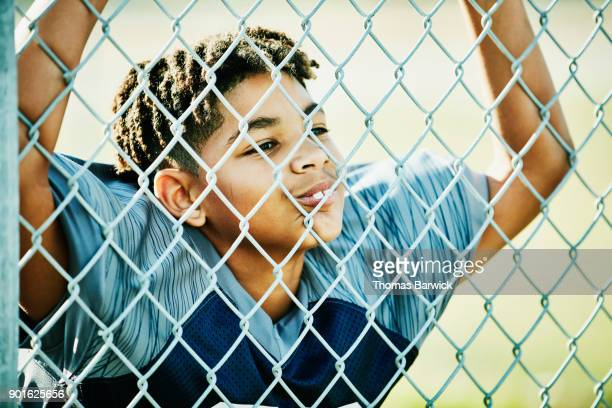 Young football player hanging on fence before football practice