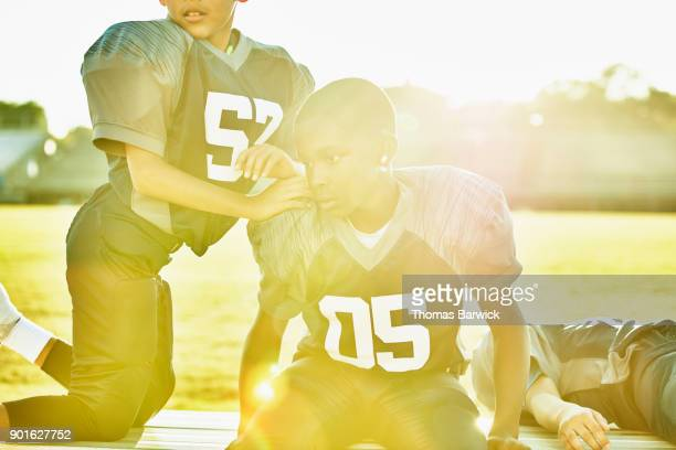 Young football player hanging out on bench with teammates before football game