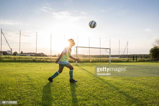 young football player heading the ball on football ground at sunset - voetbalveld stockfoto's en -beelden