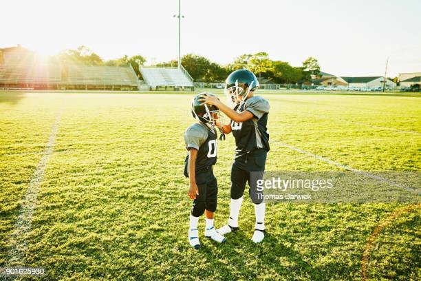 Young football player helping teammate adjust helmet before football practice on field