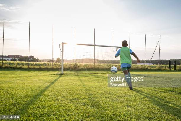 young football player on football ground at sunset - tor schießen stock-fotos und bilder